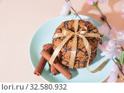 Fresh baked oatmeal cookies on a blue plate on a peach background and a branch of a blossoming apple tree. Delicious healthy culinary sweet dessert for a romantic festive breakfast, food. Стоковое фото, фотограф Светлана Евграфова / Фотобанк Лори