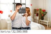 Купить «happy couple in white t-shirts with clapperboard», фото № 32580988, снято 6 октября 2019 г. (c) Syda Productions / Фотобанк Лори