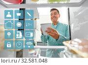 man making list of necessary food at home fridge. Стоковое фото, фотограф Syda Productions / Фотобанк Лори
