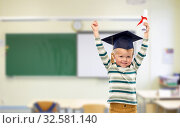 Купить «little boy in mortar board with diploma at school», фото № 32581140, снято 28 сентября 2019 г. (c) Syda Productions / Фотобанк Лори
