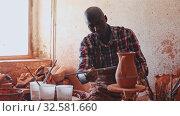 Купить «Woman and man potters putting in order crafts in pottery studio», видеоролик № 32581660, снято 4 апреля 2020 г. (c) Яков Филимонов / Фотобанк Лори