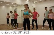 Купить «Group of teenagers participating in dance class, following their young female teacher in dance school», видеоролик № 32581952, снято 21 сентября 2019 г. (c) Яков Филимонов / Фотобанк Лори