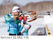 Купить «Sportsman biathlete aiming rifle shooting in standing position. Kazakhstan biathlete Kireyev Vladislav in shooting range Junior biathlon competitions East of Cup», фото № 32582116, снято 14 апреля 2019 г. (c) А. А. Пирагис / Фотобанк Лори