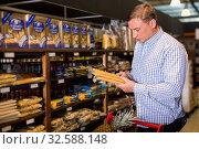 Купить «Adult man is choosing pasta in the store», фото № 32588148, снято 9 октября 2019 г. (c) Яков Филимонов / Фотобанк Лори