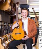 Купить «Middle-aged man choosing best acoustic guitar in musical shop», фото № 32588196, снято 29 марта 2017 г. (c) Яков Филимонов / Фотобанк Лори