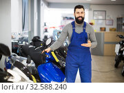 Male worker shows a variety of motorcycles. Стоковое фото, фотограф Яков Филимонов / Фотобанк Лори