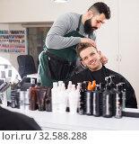Young man hairdresser making haircut to client. Стоковое фото, фотограф Яков Филимонов / Фотобанк Лори