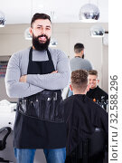 Young happy guy displaying his workplace at hairdressing salon. Стоковое фото, фотограф Яков Филимонов / Фотобанк Лори