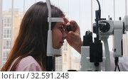 Купить «Ophthalmology treatment - a young woman checking her visual acuity - pupil reaction to light throw the lens», видеоролик № 32591248, снято 20 февраля 2020 г. (c) Константин Шишкин / Фотобанк Лори