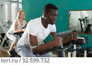 Купить «Couple training on exercise bikes», фото № 32599732, снято 25 февраля 2019 г. (c) Яков Филимонов / Фотобанк Лори