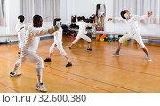 Купить «Coaches demonstrating to young athletes attack movements with rapier during fencing workout», фото № 32600380, снято 30 мая 2018 г. (c) Яков Филимонов / Фотобанк Лори
