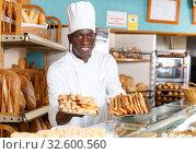 Купить «Baker in white uniform presenting baked products», фото № 32600560, снято 12 ноября 2018 г. (c) Яков Филимонов / Фотобанк Лори