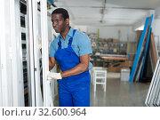 Купить «Adult man master is looking on modern window frame», фото № 32600964, снято 16 мая 2018 г. (c) Яков Филимонов / Фотобанк Лори