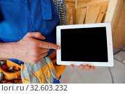 Construction worker pointing at digital tablet at construction site. Стоковое фото, фотограф Zoonar.com/Tatiana Badaeva / easy Fotostock / Фотобанк Лори