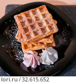 Купить «Sweet delicious dessert, homemade baked goods for breakfast. Belgian European soft waffles on a black plate and meringue», фото № 32615652, снято 30 ноября 2019 г. (c) Светлана Евграфова / Фотобанк Лори