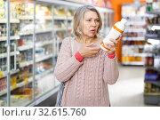 Купить «Shocked ordinary female reading product label», фото № 32615760, снято 8 февраля 2019 г. (c) Яков Филимонов / Фотобанк Лори