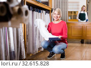 Купить «Beautiful woman choosing interesting fabric», фото № 32615828, снято 15 февраля 2017 г. (c) Яков Филимонов / Фотобанк Лори