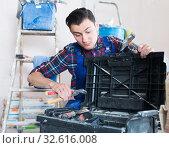 Купить «Worker looking fo tool in toolbox», фото № 32616008, снято 21 мая 2017 г. (c) Яков Филимонов / Фотобанк Лори