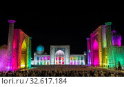 Tourists on Registan Square in Samarkand with Ulugbek Madrasah, Sherdor Madrasah and Tilla-Kari Madrasah at night during a color show. Uzbekistan (2019 год). Редакционное фото, фотограф Наталья Волкова / Фотобанк Лори