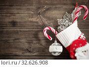 Купить «Christmas stocking with gifts hanging on dark old wooden background», фото № 32626908, снято 13 ноября 2019 г. (c) Майя Крученкова / Фотобанк Лори