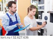 Купить «woman selecting safe with shopman», фото № 32627636, снято 17 апреля 2018 г. (c) Яков Филимонов / Фотобанк Лори