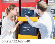Купить «Attractive woman with boyfriend looking for new reliable safe box», фото № 32627640, снято 17 апреля 2018 г. (c) Яков Филимонов / Фотобанк Лори