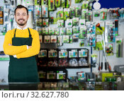 Купить «Seller displaying various items in garden equipment shop», фото № 32627780, снято 2 марта 2017 г. (c) Яков Филимонов / Фотобанк Лори