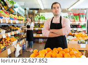 Купить «Man in apron selling fresh oranges and fruits on the supermarket», фото № 32627852, снято 27 апреля 2019 г. (c) Яков Филимонов / Фотобанк Лори