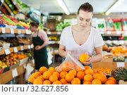 Купить «Woman customer choosing fresh oranges on the supermarket», фото № 32627856, снято 27 апреля 2019 г. (c) Яков Филимонов / Фотобанк Лори