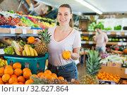 Купить «Young woman standing with full grocery cart during shopping», фото № 32627864, снято 27 апреля 2019 г. (c) Яков Филимонов / Фотобанк Лори