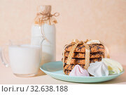 Fresh baked oatmeal crispy cookies on a blue plate on a background of peach color, milk, French multi-colored meringues. Delicious culinary sweet dessert for breakfast, food, snacks. Стоковое фото, фотограф Светлана Евграфова / Фотобанк Лори