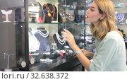 Купить «Stylish female client choosing elegant necklace from natural pearls in jewelry shop», видеоролик № 32638372, снято 31 октября 2019 г. (c) Яков Филимонов / Фотобанк Лори