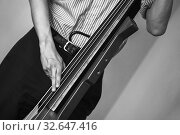 Купить «Man plays red modern electric contrabass in musical studio», фото № 32647416, снято 18 мая 2019 г. (c) EugeneSergeev / Фотобанк Лори
