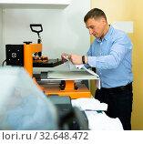 Купить «Man using a serigraph press to print a shirt in a workshop», фото № 32648472, снято 3 августа 2020 г. (c) Яков Филимонов / Фотобанк Лори