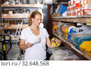 Купить «Woman customer holding shop list and looking tools at shelves», фото № 32648568, снято 20 сентября 2018 г. (c) Яков Филимонов / Фотобанк Лори
