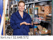 Young woman worker in uniform showing construction materials in store. Стоковое фото, фотограф Яков Филимонов / Фотобанк Лори