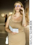 Купить «Female visitor with information booklet», фото № 32648604, снято 22 сентября 2018 г. (c) Яков Филимонов / Фотобанк Лори