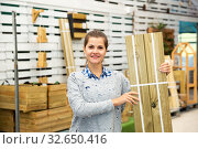 Купить «Woman choosing wooden panels at gardening store», фото № 32650416, снято 3 июня 2020 г. (c) Яков Филимонов / Фотобанк Лори