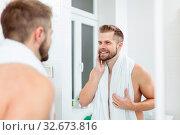 Morning hygiene, Handsome man in the bathroom looking in mirror. Стоковое фото, фотограф Zoonar.com/Tomas Anderson / easy Fotostock / Фотобанк Лори