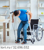Young man recovering after surgery at home with crutches and a w. Стоковое фото, фотограф Elnur / Фотобанк Лори