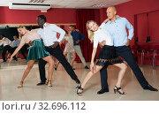 Купить «Portrait of positive adult pairs enjoying tango in modern dance hall», фото № 32696112, снято 4 октября 2018 г. (c) Яков Филимонов / Фотобанк Лори