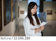 Купить «Chinese female visitor with guide-book looking at artwork painting», фото № 32696288, снято 24 февраля 2020 г. (c) Яков Филимонов / Фотобанк Лори