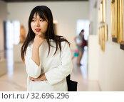 Купить «Serious chinese female visitor looking at artwork painting in museum», фото № 32696296, снято 24 февраля 2020 г. (c) Яков Филимонов / Фотобанк Лори
