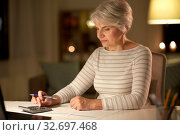 Купить «old woman counting on calculator at home at night», фото № 32697468, снято 14 ноября 2019 г. (c) Syda Productions / Фотобанк Лори