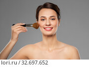 Купить «beautiful woman with makeup brush applying blusher», фото № 32697652, снято 30 ноября 2019 г. (c) Syda Productions / Фотобанк Лори