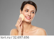 Купить «young woman cleaning face with exfoliating sponge», фото № 32697656, снято 30 ноября 2019 г. (c) Syda Productions / Фотобанк Лори
