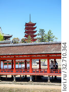 Red builds and passages is against five-storied Japanese style Pagoda Gojunoto are in Itsukushima. Miyajima the Shrine Island lies within Setonaikai National Park (2013 год). Редакционное фото, фотограф Кекяляйнен Андрей / Фотобанк Лори
