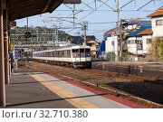 Old train by West Japan Railway Company (JR West) comes to Miyajimaguchi Station. It is on Sanyo Main in Hatsukaichi, Hiroshima. Way to Itsukushima (2013 год). Редакционное фото, фотограф Кекяляйнен Андрей / Фотобанк Лори