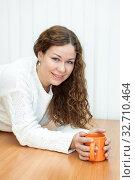 Pretty Caucasian woman dressed knitted pullover lying on table with orange mug in hands. Стоковое фото, фотограф Кекяляйнен Андрей / Фотобанк Лори