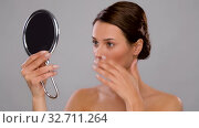 Купить «beautiful woman with mirror touching her face», видеоролик № 32711264, снято 8 декабря 2019 г. (c) Syda Productions / Фотобанк Лори